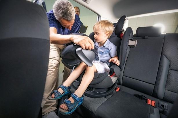 Popis: Upevňování autosedačky s dítětem.